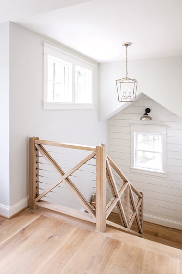 The three-level stair features cable railings and white-oak trim; the windows were sourced at Loewen Windows of Annapolis.