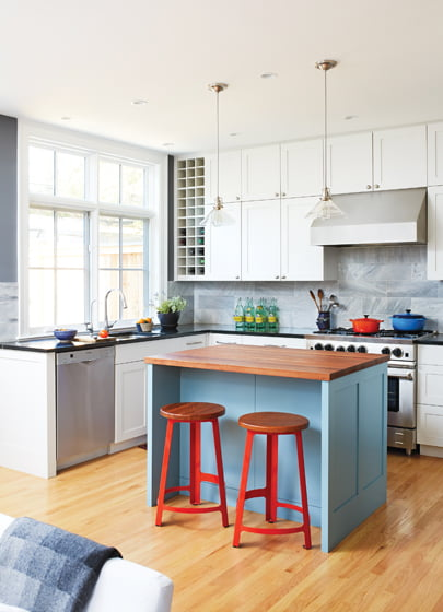 The kitchen features custom cabinets, marble backsplash, soapstone counters and an island topped with butcher block.