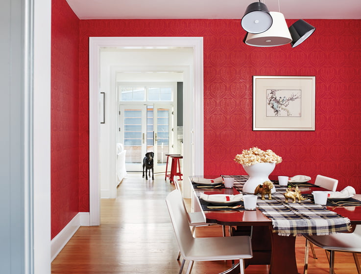 The dining room is swathed in bright-red Cole & Son wallpaper.