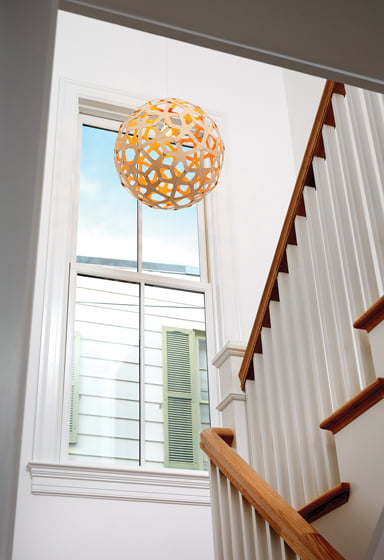 A Coral pendant by David Trubridge hangs in the new staircase, bathed in light.