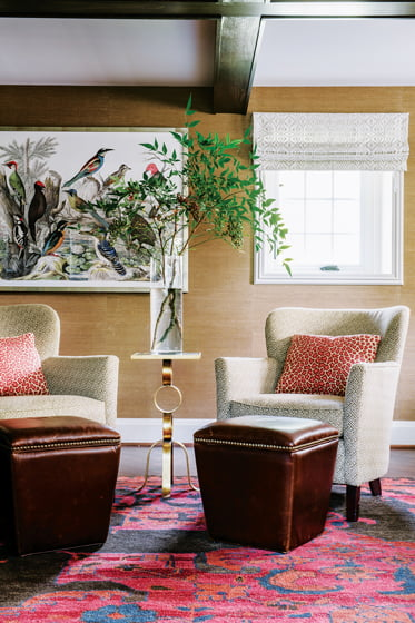 Thibaut grass-cloth wall covering and a vibrant rug make the den a cozy retreat.