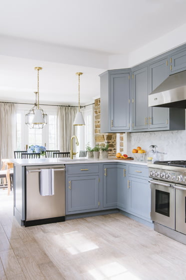 Crosby painted the cabinets blue-gray and replaced the floors with wood-look porcelain tile.