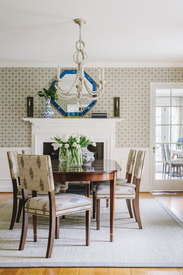 A Bunny Williams mirror and Romo wallpaper enliven the dining room.