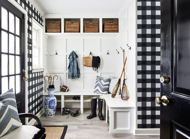 A welcoming mudroom by Tracey Morris of Gillis Interiors combines checked wallpaper and crisp, white millwork.