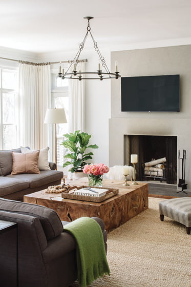 The family-room addition centers on a teak coffee table from Noir Furniture and Lee Industries sofas.
