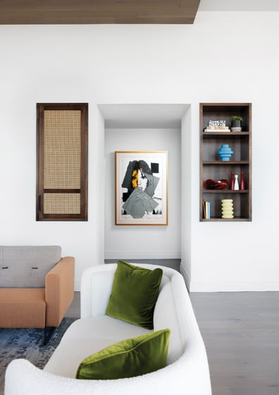 """Walnut shelving and cane-detailed storage flank a hallway with a screen print of Andy Warhol's """"Mick Jagger 147."""
