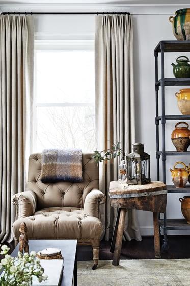 Beside a tufted-linen chair, an RH étagère showcases a collection of antique confit pots.