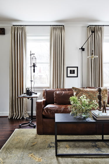 A vintage table lamp and wall sconce, both from Industrial Artifacts, pair well with the leather  RH sofa.
