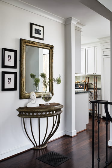 A 19th-century French mirror from Côté Jardin Antiques in Georgetown hangs over a demilune console in the hall.