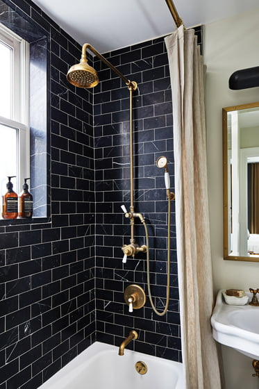 The guest bathroom boasts Nero Marquina marble subway tile.