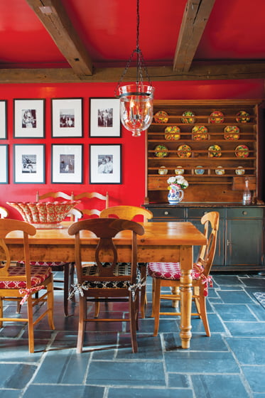 The dining area, painted in Benjamin Moore's Caliente, is filled with colorful Italian ceramic dishware by Deruta.