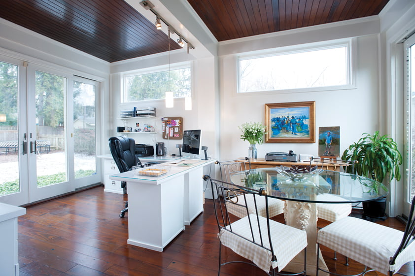 Polly works at home in a bright, converted sun room.