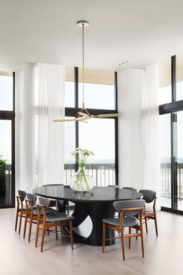 In the dining area, a sculptural table by Caleb Woodard is surrounded by Finn Juhl's 108 Chairs.