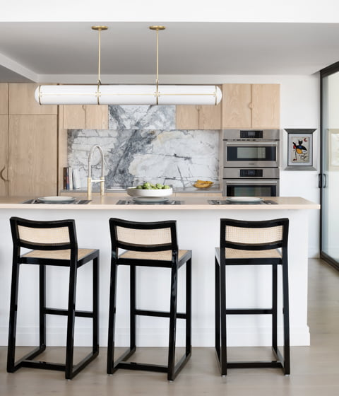 Katie Otis designed the kitchen with an island and breakfast bar, which opens to the dining room.