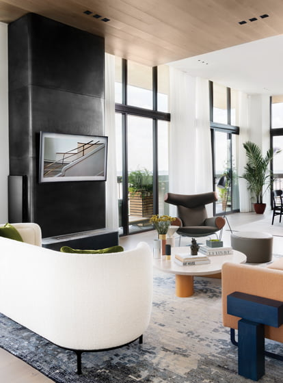 A hot-rolled-steel fireplace and Stark rug define the living area, anchored by Hans Wegner's Ox Chair.