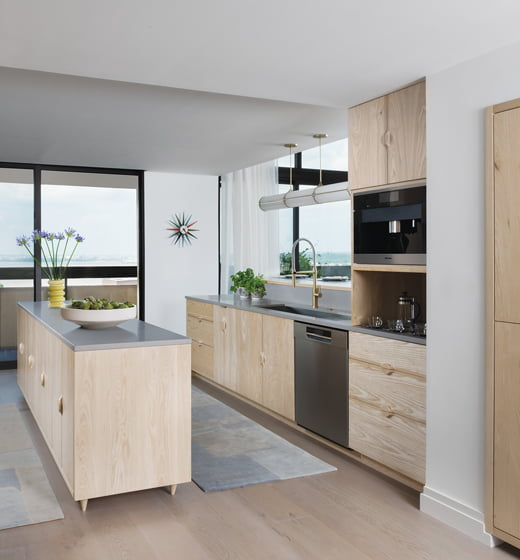 Custom, bleached-ash cabinetry keeps the kitchen's palette light; the countertops are gray honed quartz.