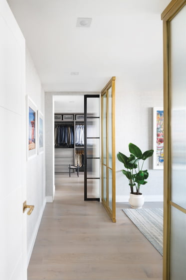 Brass-and-glass doors delineate the master bedroom, while a steel-and-glass door leads to the wardrobe.