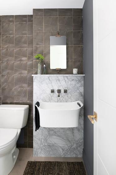 Ann Sacks tile and an integrated marble shelf animate the powder room.
