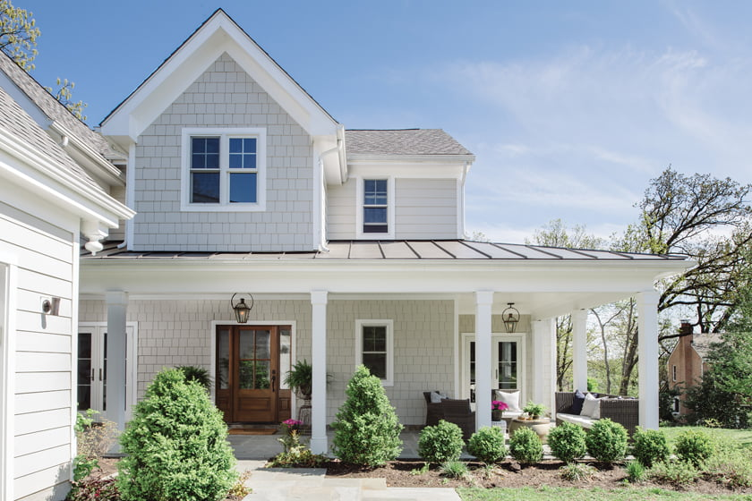 The shingled structure became a modern farmhouse with a standing-seam metal roof above a wraparound porch.