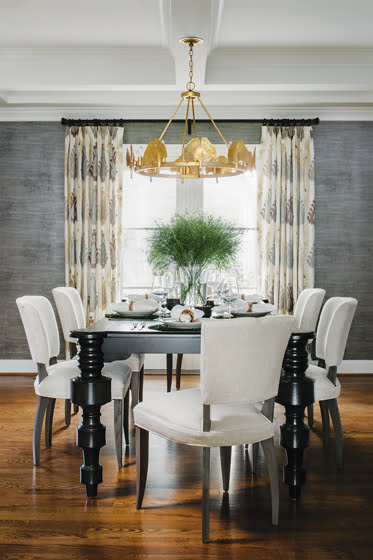 A gold Currey & Company light fixture hangs above the Noir Furniture table and Lee Industries chairs.