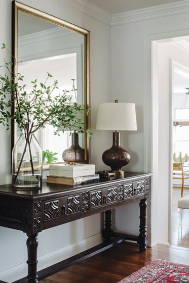 A Noir Furniture console and custom mirror adorn the entry.