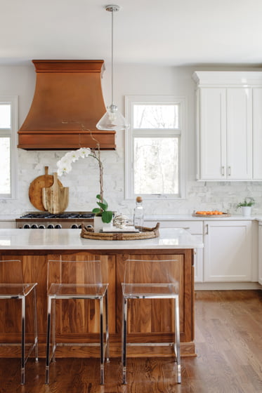 The new kitchen is organized around a walnut-paneled island topped with Calacatta Gold marble.