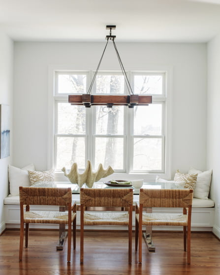 A breakfast nook boasts a built-in window seat and a chandelier from Currey & Company.