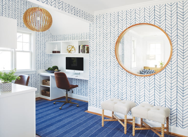 Blue carpet complements gold accents in the CB2 mirror and ottomans.