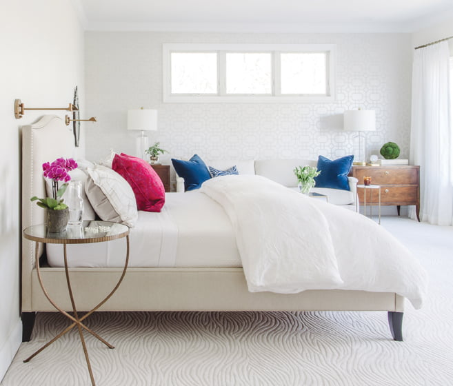 The white-on-white master bedroom is serene and restful.