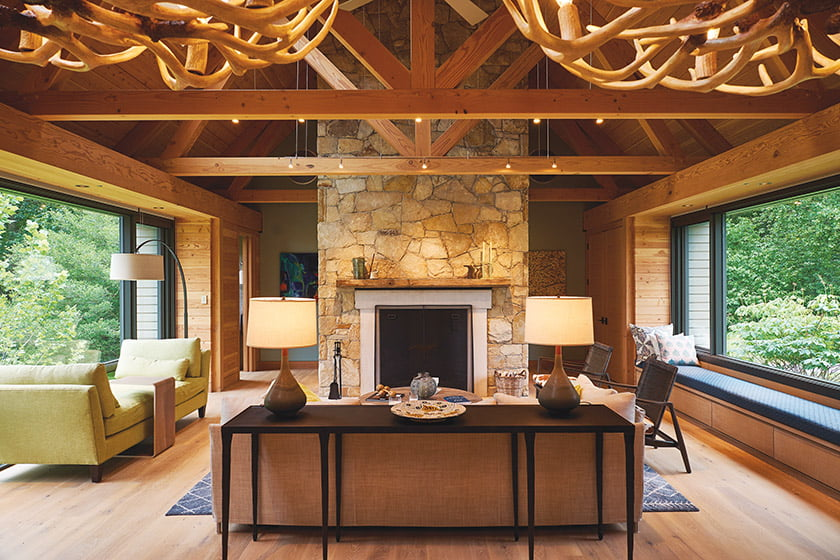 Designed by HapstakDemetriou+, a barn-like modern abode on the Chesapeake Bay. The open-plan interior is unified by natural-wood timbers and trusses.