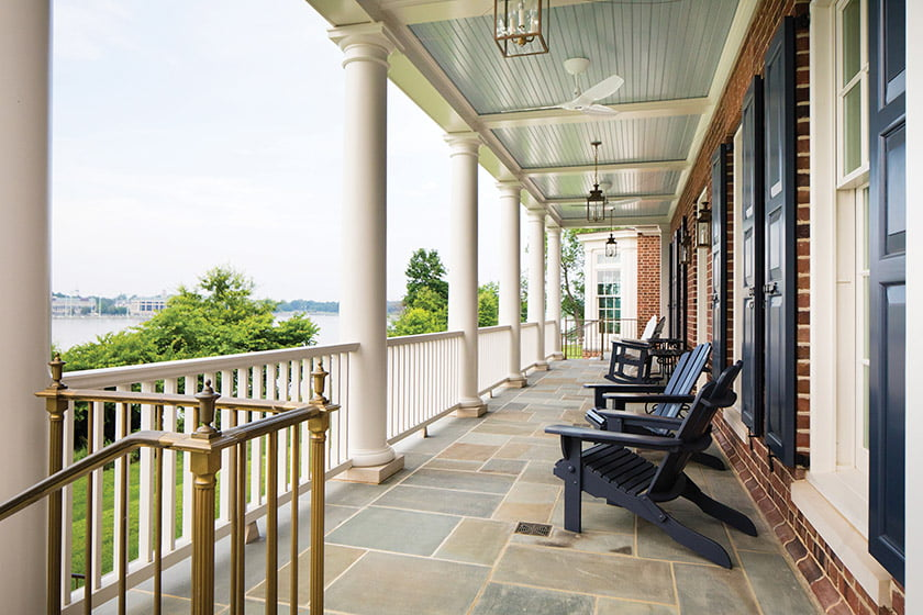 The back porch combines bluestone floors and custom bronze railings. The landscape was designed by Campion Hruby Landscape Architects. Photos by Kate Martin