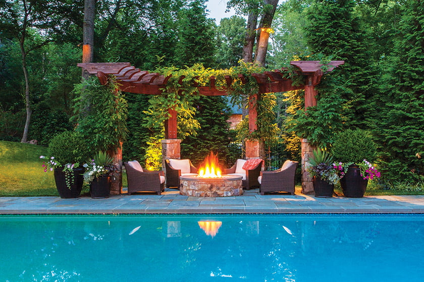 A fire pit and pergola by Wheat's Landscape. © George E. Brown