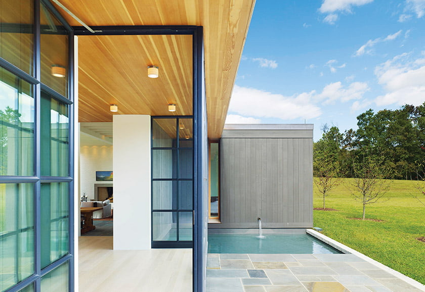 Past a courtyard and water feature, guests arrive at the entryway, its geometry detailed in stone, wood and steel.