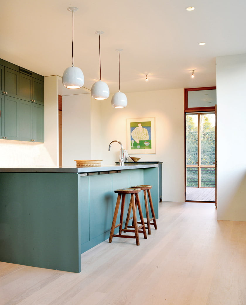 Cabinetry hand-painted in soft green lends a timeless patina to the kitchen. © Richard Williams