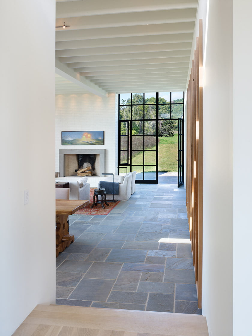Inside the airy great room, radiant-heated bluestone floors lead outside to a horse pasture and rolling foothills.