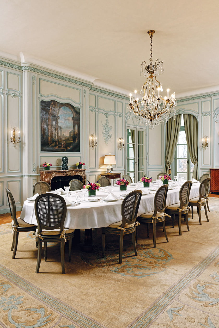 The Louis XV Rococo-style dining room features a restored, Regency-style mahogany table with 10 leaves.
