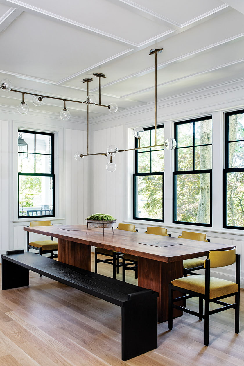 In the dining room, Lumifer lighting hangs above a Usona table, vintage chairs and a bench by Fern.