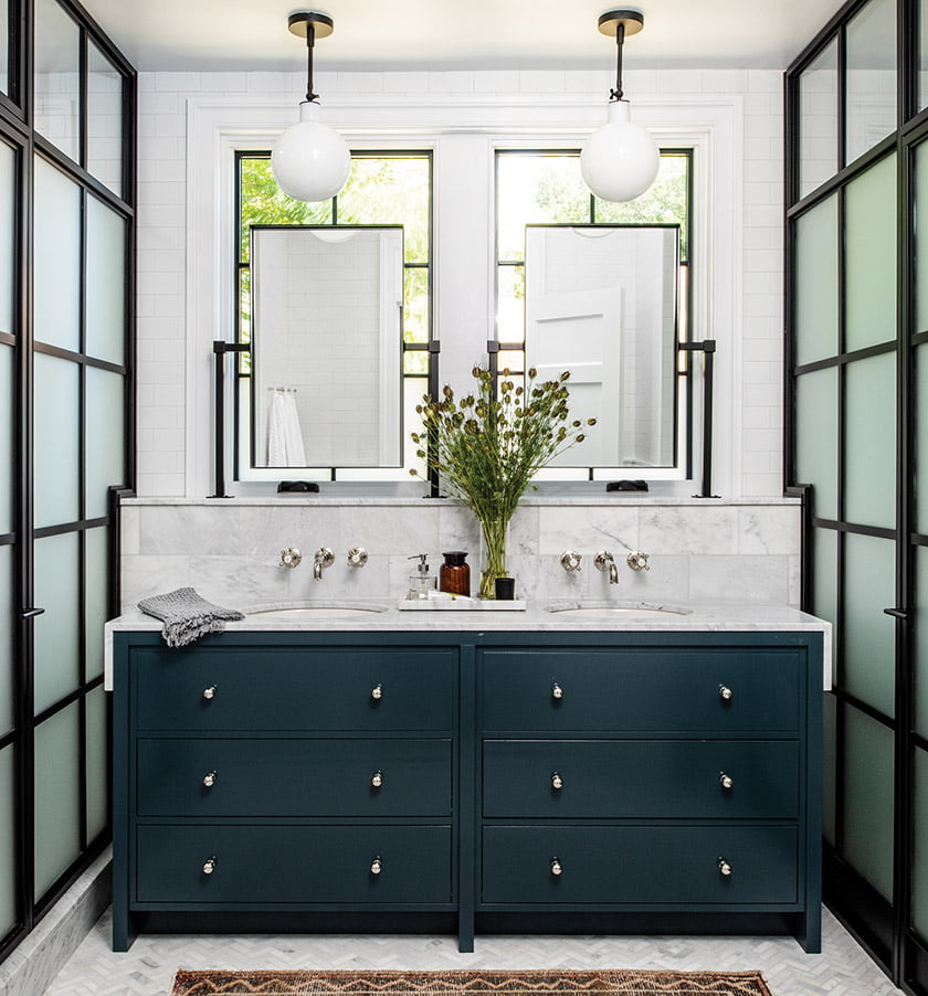 In the master bathroom, custom steel-and-glass doors screen the shower enclosure and WC.