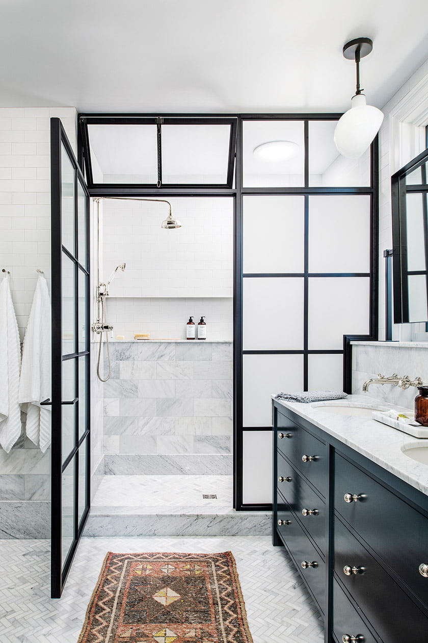 A skylight brightens  the marble-and-ceramic-tile shower, with fixtures by Waterworks.