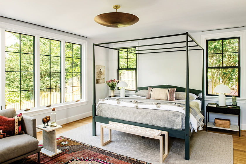 In the master bedroom, a bed by Great Windsor Chairs offers a fresh take on the traditional four-poster.
