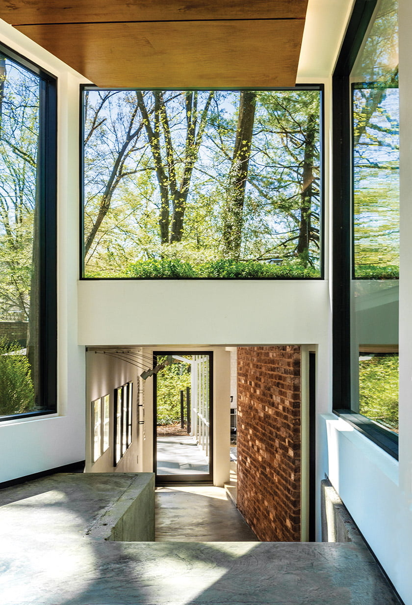 A clerestory window and glass door provide daylight and wooded views at the threshold of the addition.