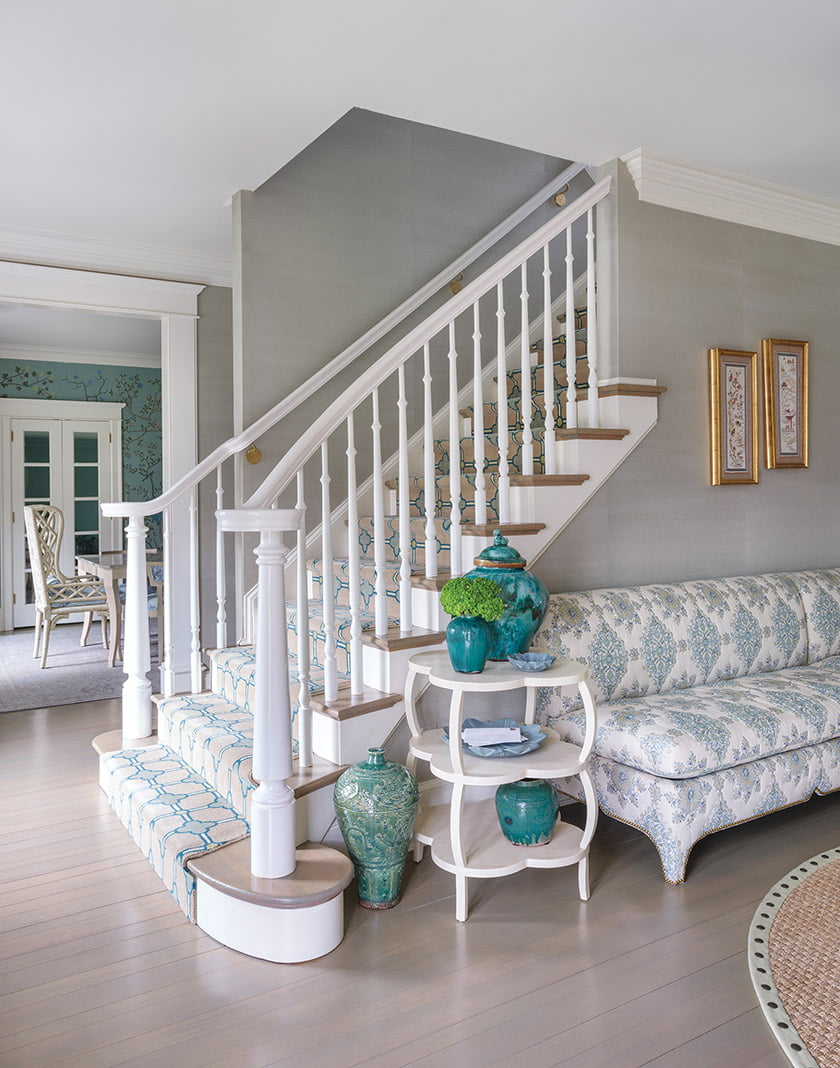 A custom stair runner and comfy sofa dress up the foyer.