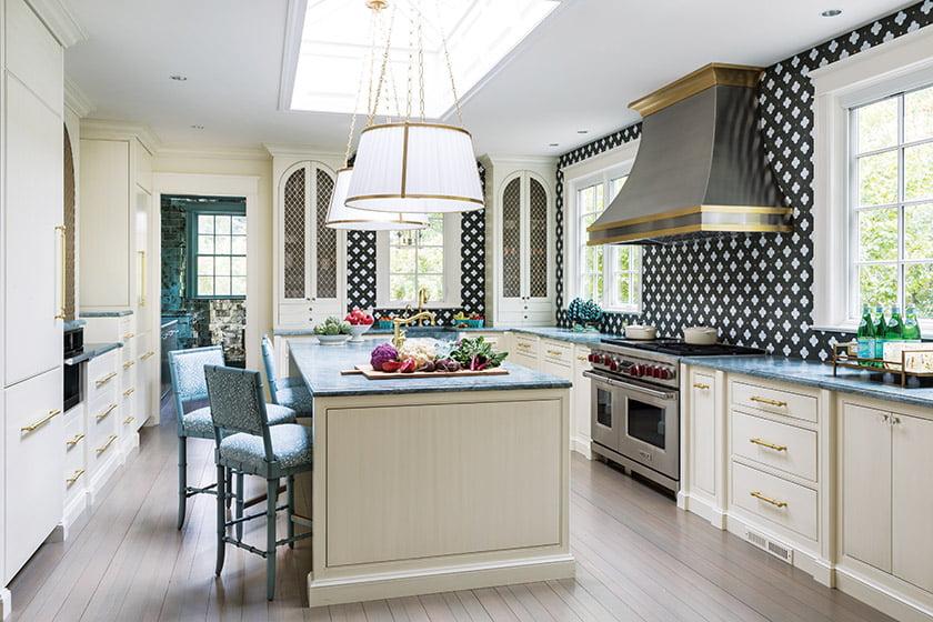 The custom kitchen backsplash is by New Ravenna; Ralph Lauren pendants hang above the island.