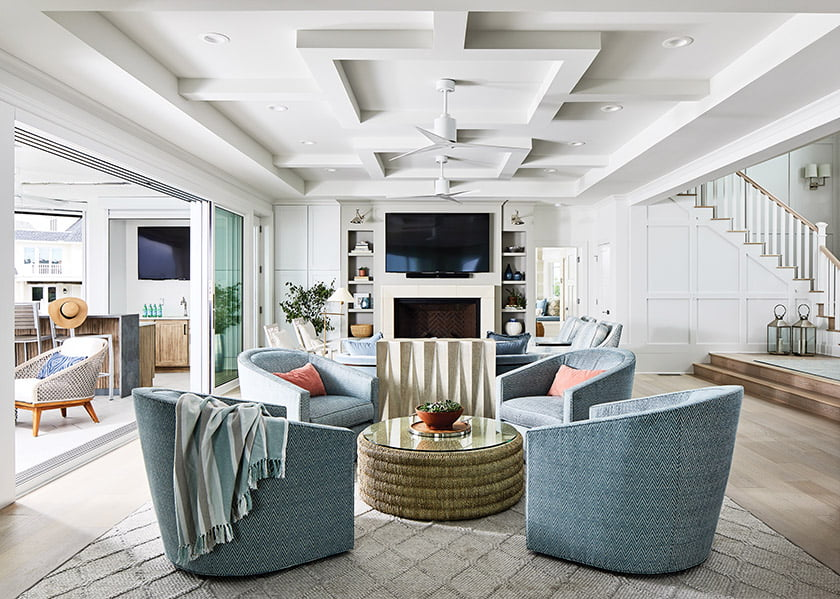 Two seating areas in the great room are unified by a rug from Coe & Son; Ambella swivel chairs facilitate TV-watching.