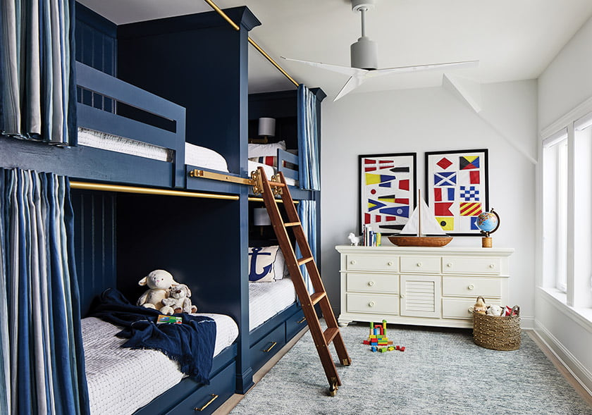 A bedroom features custom bunks, each with charging station and lamp, and a vintage rolling library ladder.