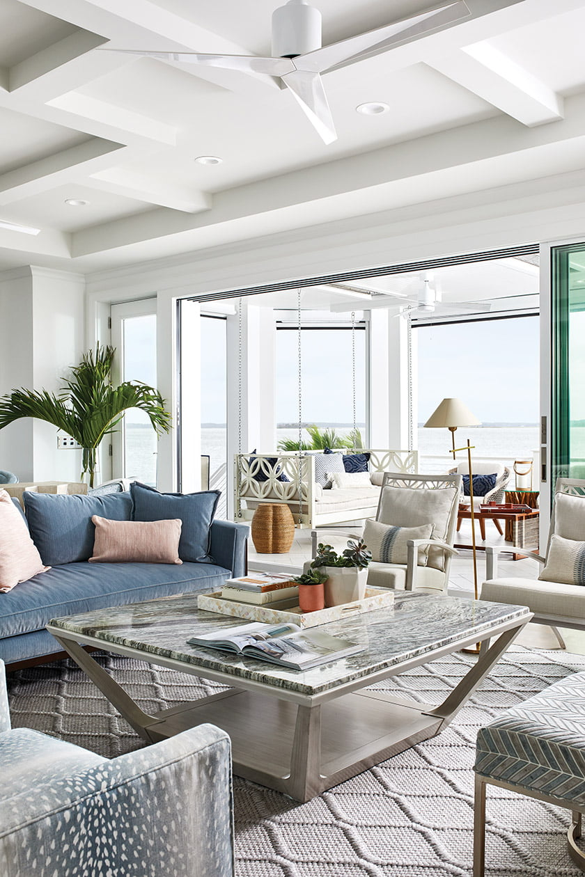 The porch flows into the great room, where a Stanley coffee table anchors a seating area with an Ambella sofa.