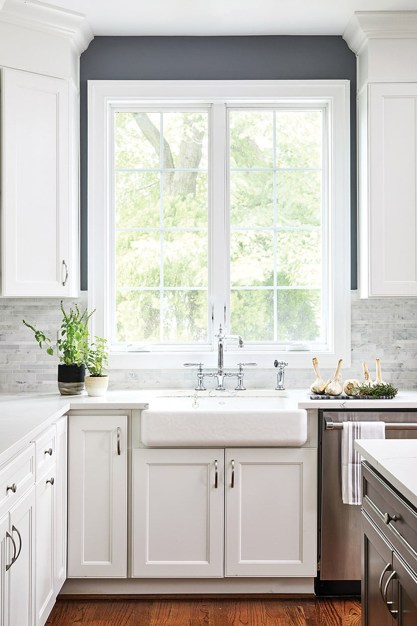 The kitchen is finished with a marble-tile backsplash and a porcelain farmhouse sink.