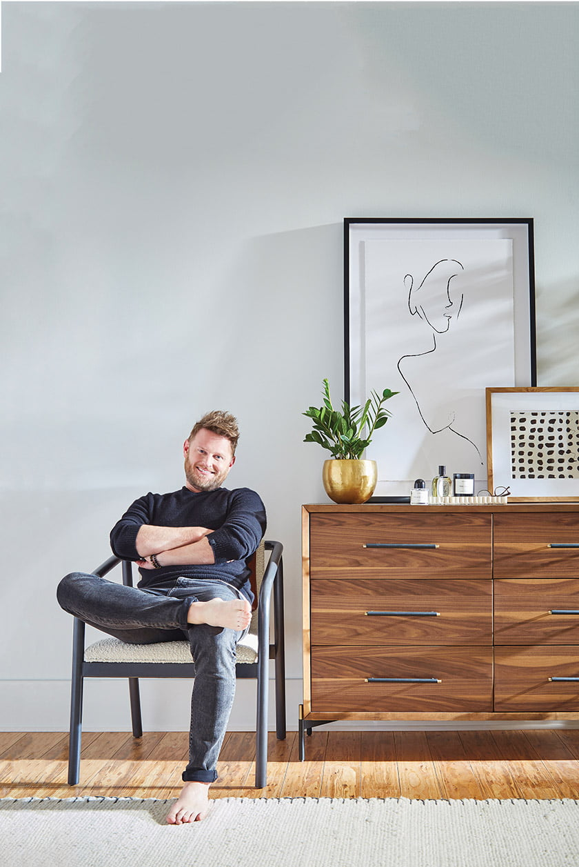 Bobby Berk relaxes in the Sanni Chair with the Gehl dresser beside him.
