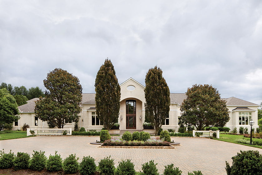The French manor-style home features a façade of ivory brick and stucco.