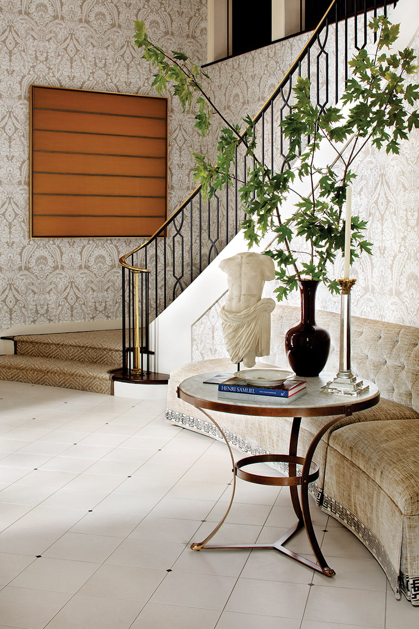 Damask wall covering by Cole & Son is juxtaposed with a contemporary canvas by Tom Bolles in the foyer.